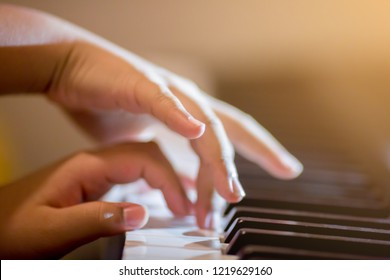 Selective focus of kid fingers and  piano key to play the piano with lighting. There are musical instrument for concert or learning music.