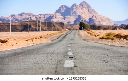 (selective focus) Kings highway, beautiful road running through the Wadi Rum desert with rocky mountains in the distance, Jordan.