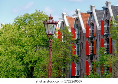 Selective focus of lamp post in Amsterdam in spring with blurred view of architecture traditional canal houses, Old warehouse with red windows (Pakhuis) at Prinsengracht as background, Netherlands.