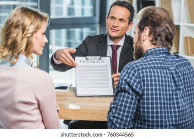selective focus of lawyer pointing at contract wile showing it to clients in office