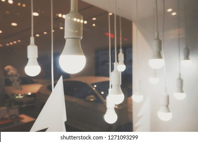 Selective focus of LED modern hanging energy light bulbs decorative with car show room background on interior decorations design concept