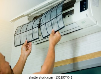 selective focus to left hand of male technician cleaning air conditioner indoors with a lot of dust. Basic cleaning dust in air conditioner at home with yourself.