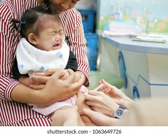 Selective focus of little Asian baby girl, one year old, crying in pain while pediatric nurses securing her leg and giving her a vaccination