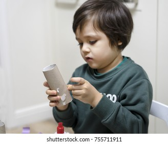 Selective focus of little boy building the rocket paper toys for his home work, Blurry Child showing his hand made rocket toy from a toilet roll, Children or Toddler learning and Development concept