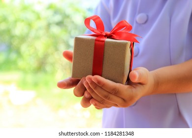 Selective focus of Little girl hands holding gift box with red ribbon for Christmas  and New Year's Day or Greeting season