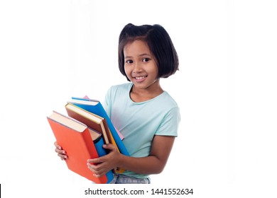Selective focus lovely Asian schoolgirl have fun holding stack of books over head,. smart EQ kid girl look stack of books or homework,  kid, educations, back to school on white isolated background