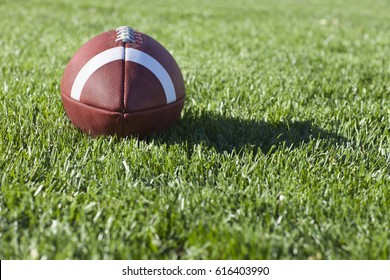 Selective focus, low angle view of a college style football on a grass field