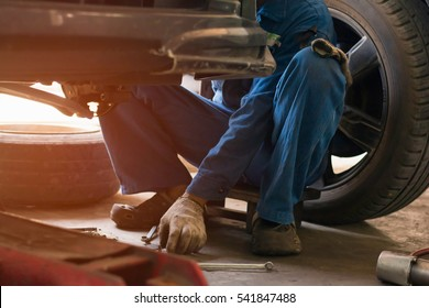 Selective focus low key  young man using tool  for repair brake car  a part of wheel tire in garage.