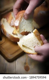 Selective focus. Macro. A piece of fresh wheat bread in the hands. Fresh loaf.