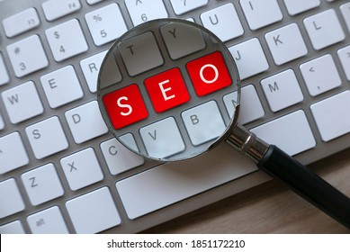 Selective focus of magnifying glass and computer keyboard with red key written with SEO Search Engine Optimization on a wooden background.