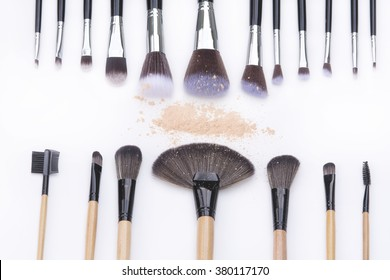 Selective focus makeup brushes and makeup powder on white backgrounds