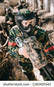 selective focus of male paintball player in goggle mask and camouflage aiming by paintball gun from ditch outdoors