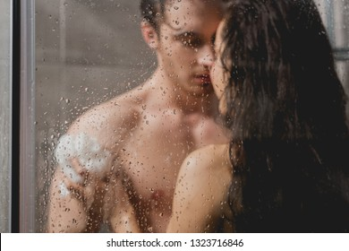 selective focus of man and beautiful woman hugging and taking shower with loofah in cabin