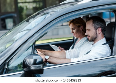 selective focus of man driving car while woman using digital tablet