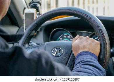 Selective focus of man driving a taxi. View from inside the taxi car. closeup from inside the car of taxi driver during rush hour in Beijing downtown, China. 12/09/2018