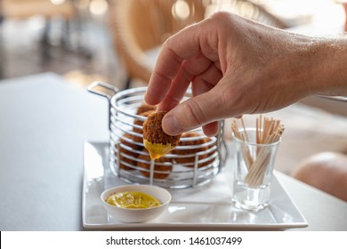 Selective focus of a man hand with the bitterballen, Dutch meat-based snack served with mustard, typically containing a mixture of beef or veal, Bitterballen are one of Holland's favorite snacks.