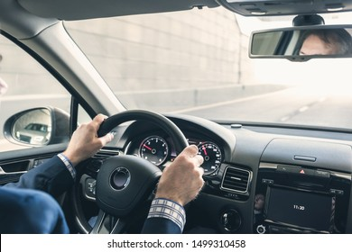 Selective focus of man hands on steering wheel driving a car on the speed highway. View from above