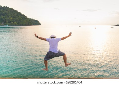 Selective focus man jumping off wooden into the ocean. Summer fun lifestyle.concept freedom of life.