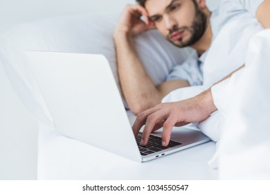 selective focus of man lying on bed and using laptop