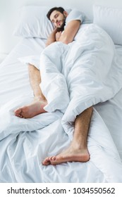 selective focus of man sleeping on white bed