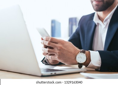 selective focus of man using smartphone with laptop on table