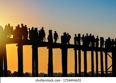 Selective focus, Mandalay, Myanmar (Burma), Sunset with silhouettes people U bein Bridge in Amarapura across Ayeyarwady Riverin. U-bein Bridge is oldest and longest teak wooden bridge in the world