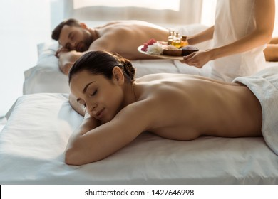 selective focus of masseur holding tray with sea salt and bottles of oil near woman and man in spa center