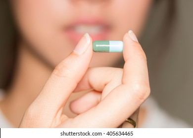 selective focus Medicine pills or capsules in hand, palm or fingers. Drug prescription for treatment medication. Woman, young female, person taking vitamin, painkiller, antibiotic