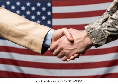 selective focus men shaking hands near american flag