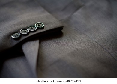 A selective focus of  men suit, soft focus of button on sleeve, light grey color of suit