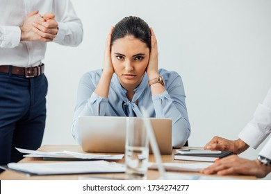 Selective focus of mexican businesswoman covering ears near multiethnic colleagues in office