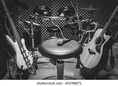 selective focus the  microphone on chair and musical instrument the guitar,electric drum,bass,speakers,background. music production band concept.