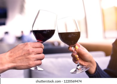 selective focus of Mid adult Caucasian male and female hands toasting wine glasses in the room on the Boat cruises.