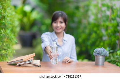 In selective focus of mineral water in Attractive young woman hand holding and giving to camera.