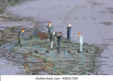 Selective focus of miniature businessman handshake on Brazil map background as commitment, agreement and partnership Concept