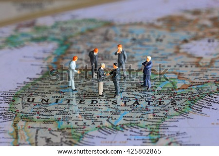 Selective focus of miniature businessman handshake on United State (USA) map background as commitment, agreement and travel Concept