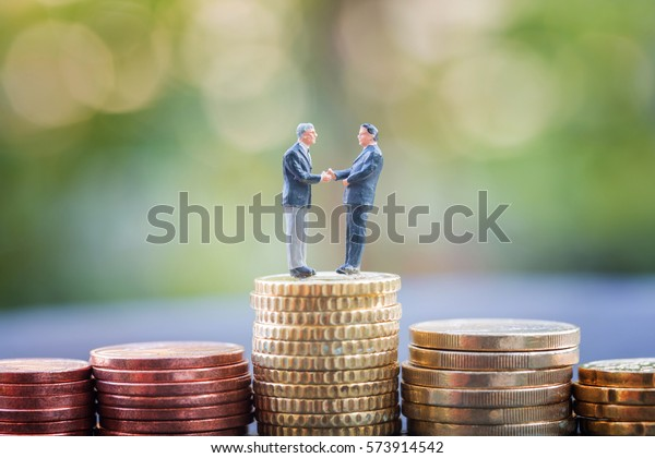 Selective focus of miniature businessman handshake on Euro coins stacks as business , commitment, investment, teamwork and partnership concept