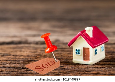 selective focus of miniature tiny home with red pin and sold tag on wooden floor,  Image for real-estate management  concept.