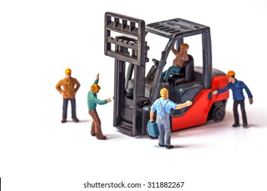 selective focus of miniature worker holding bag and standing front of forklift machine, on white background.