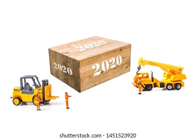 Selective focus of Miniature Worker People, Working  front of forklift machine with Wood Box, on white background