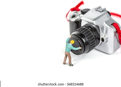 selective focus of miniature worker with plastic camera toy on white background.