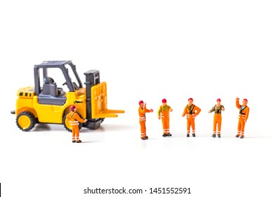 selective focus of miniature worker  standing front of forklift machine, on white background.