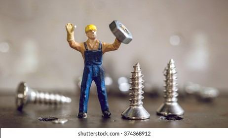 selective focus of miniature worker working with nut and screw,macro photography. vintage color tone.