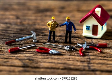 selective focus of miniature worker working with tool tools supplies and tiny home model  on wooden floor,macro photography concept idea for solution of property management service.