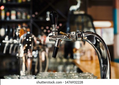 Selective focus of modern beer taps in pub. Closeup of beer pumps standing in cafe in evening. Professional equipment in brewery. Concept of beer, ale, alcohol and service.