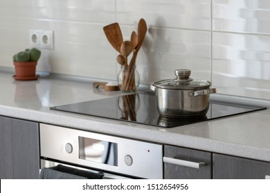 Selective focus of modern house with design interior, built in kitchen appliance and white tile on wall. Black ceramic induction stove with saucepan on clean surface, wooden supplies and green cactus