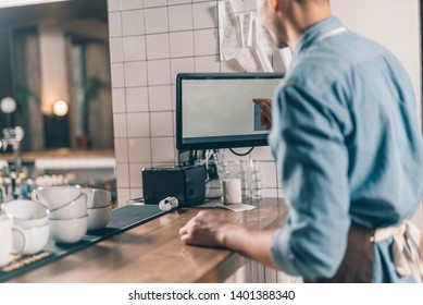 Selective focus of a modern monitor at the bar counter in a cafe and professional barista using it