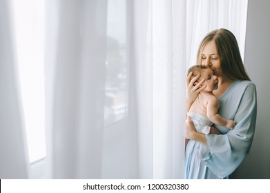 selective focus of mother kissing adorable baby boy in front of curtains at home