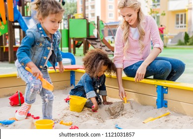 selective focus of mother playing with daughter and her little friend in sandbox at playground