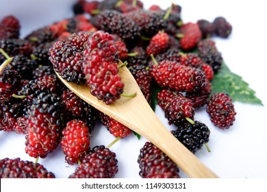 Selective focus mulberry on wooden spoon and blurred mulberry and leaf background.